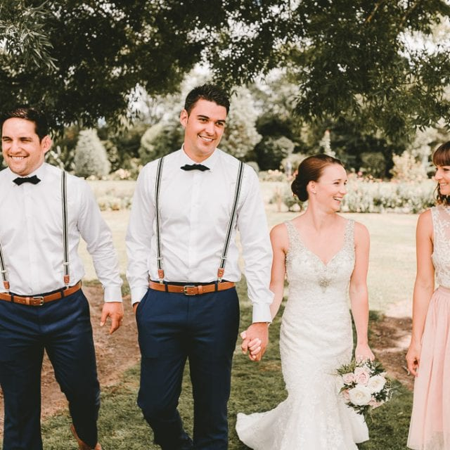Groom in bowtie and bride with hair up in a stunning wedding dress walking with the bridal party.