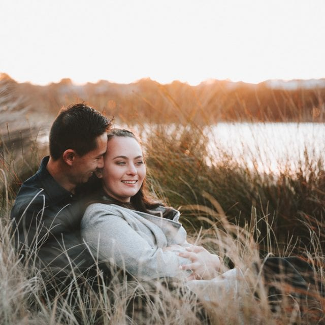 Engaged couple sit in long grass at sunset near the ocean at Maraetai.